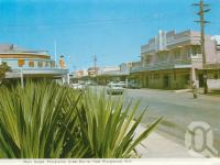 """<span class=""""caption-caption"""">Main Street, Proserpine</span>, c1970. <br />Postcard folder by <span class=""""caption-publisher"""">Murray Views Pty Ltd</span>, collection of <span class=""""caption-contributor"""">Centre for the Government of Queensland</span>."""