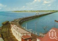 "<span class=""caption-caption"">Wharf and pier at Urangan</span>, c1970. <br />Postcard by <span class=""caption-publisher"">Murray Views Pty Ltd</span>, collection of <span class=""caption-contributor"">Centre for the Government of Queensland</span>."