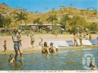 "<span class=""caption-caption"">The beach at Lake Moondarra, Mount Isa</span>, c1972. <br />Postcard folder by <span class=""caption-publisher"">Murray Views Pty Ltd</span>, collection of <span class=""caption-contributor"">Centre for the Government of Queensland</span>."