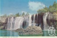 "<span class=""caption-caption"">Millstream Falls near Ravenshoe</span>, c1960. <br />Postcard folder by <span class=""caption-publisher"">Murray Views Pty Ltd</span>, collection of <span class=""caption-contributor"">Centre for the Government of Queensland</span>."