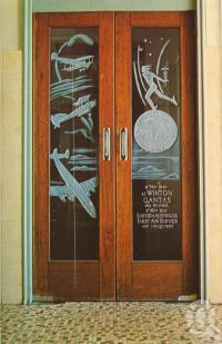 "<span class=""caption-caption"">Qantas Memorial Doors, North Gregory Hotel, Winton</span>, c1960. <br />Postcard folder by <span class=""caption-publisher"">Murray Views Pty Ltd</span>, collection of <span class=""caption-contributor"">Centre for the Government of Queensland MS</span>."