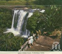 """<span class=""""caption-caption"""">Mena Creek Falls, Paronella Park</span>, c1958. <br />Postcard folder by <span class=""""caption-publisher"""">GK Bolton</span>, collection of <span class=""""caption-contributor"""">Centre for the Government of Queensland</span>."""