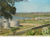 "<span class=""caption-caption"">Alumina Plant and oil storage from Auckland Park, Gladstone</span>, c1975. <br />Postcard folder by <span class=""caption-publisher"">Murray Views Pty Ltd</span>, collection of <span class=""caption-contributor"">Centre for the Government of Queensland</span>."